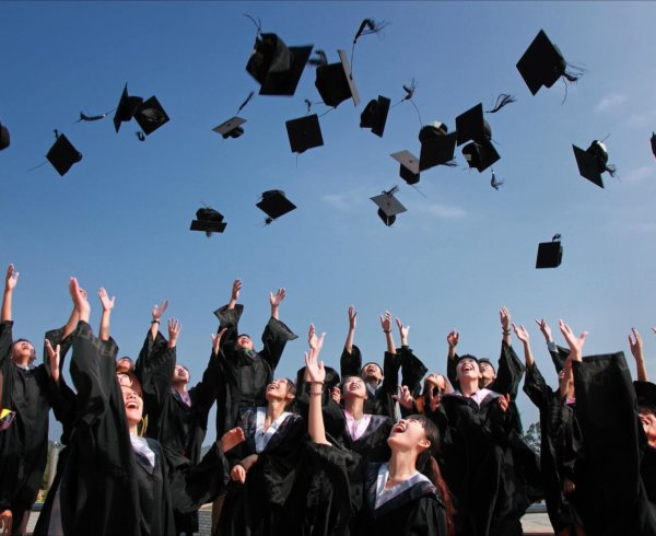 Students graduating and throwing caps in the air