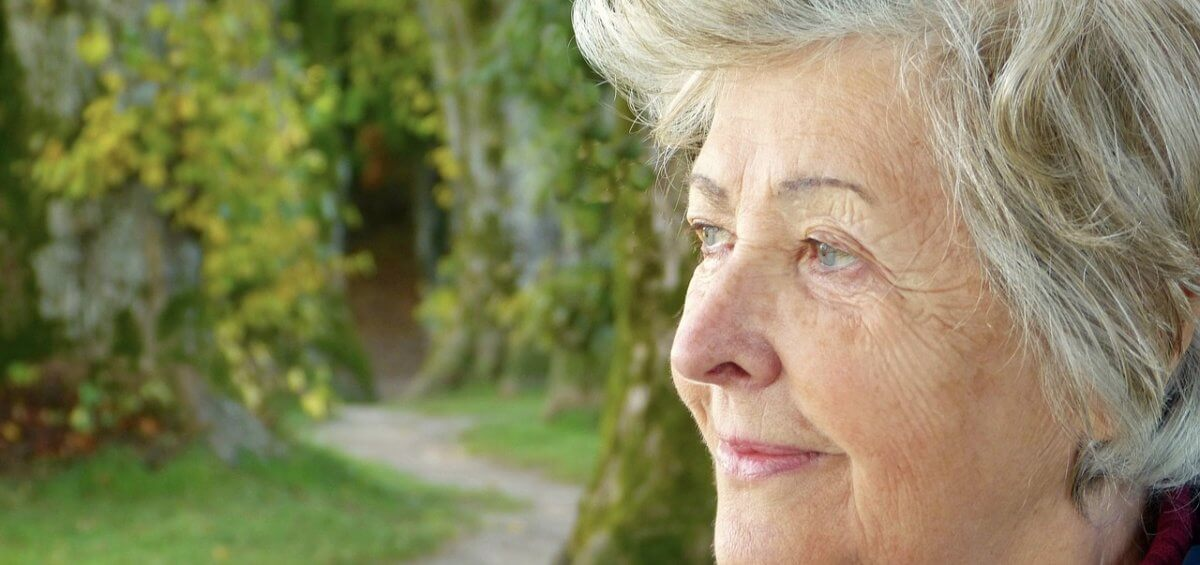 older woman thinking about her gazing in a park