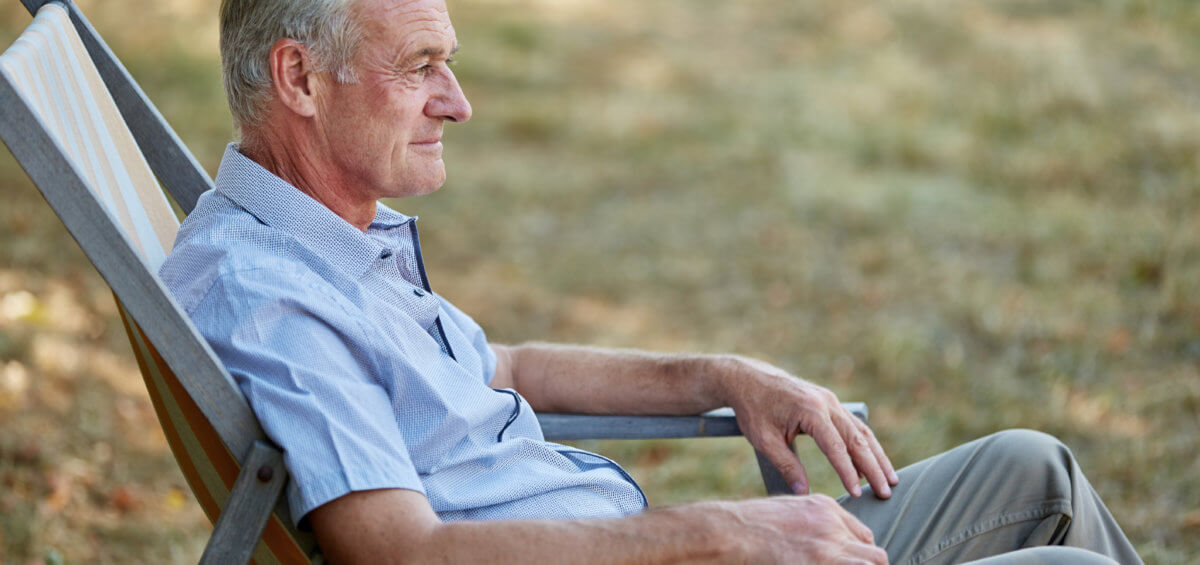 Old man sitting relaxed on a deck chair