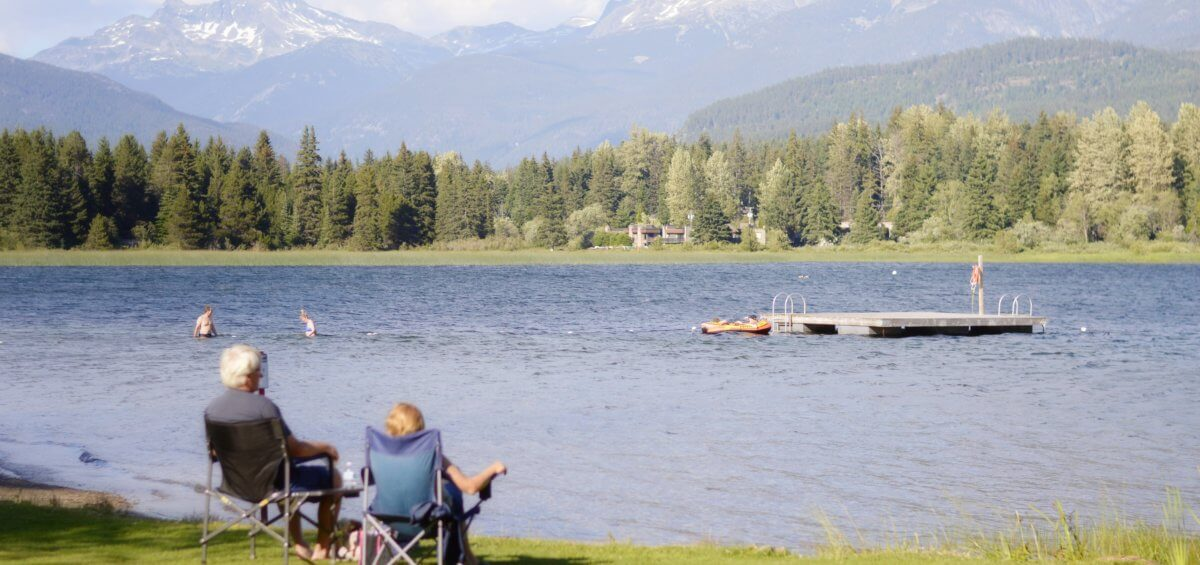 older couple siting by a lake looking at the mountains