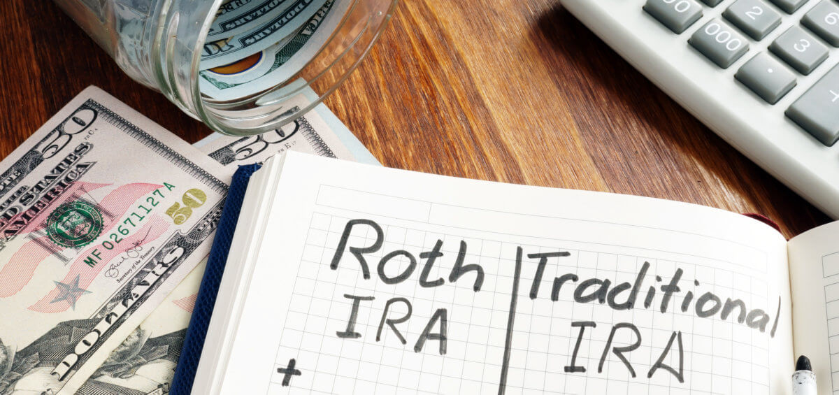 notepad traditional ira vs roth ira money and calculator on wooden surface