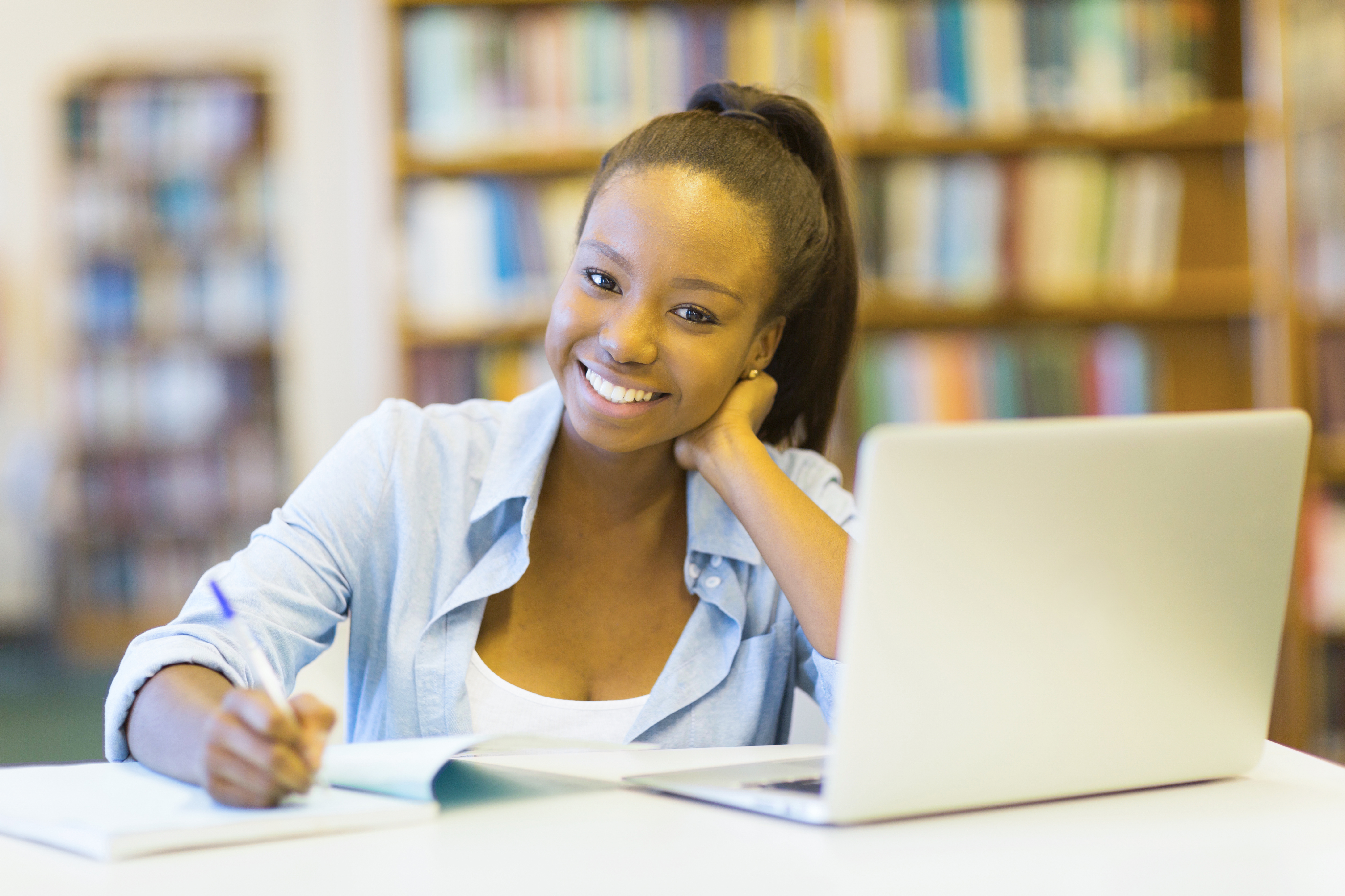 girl with ponytail smiling and writing in a notebook in front of a laptop she's smart and doesn't have to worry about exams