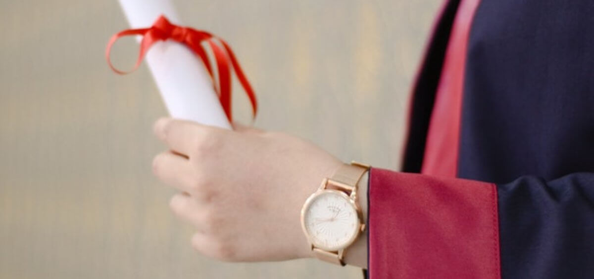 Hand with watch holding diploma